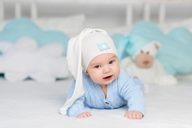 Een baby op een bed in een kap gaat naar bed of wordt 's ochtends wakker. textiel en beddengoed voor kinderen. pasgeboren baby met een stuk speelgoed beer