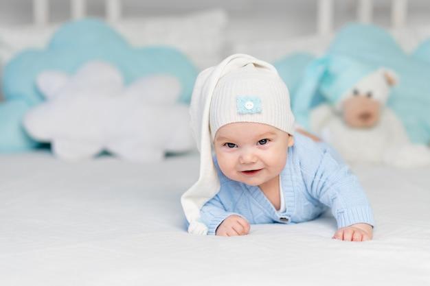 Een baby op een bed met een capuchon gaat naar bed of wordt 's ochtends wakker. textiel en beddengoed voor kinderen. pasgeboren baby met een speelgoedbeer