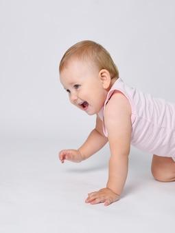Een baby op een witte achtergrond leert de eerste stapjes van een jaar oud kindje te kruipen