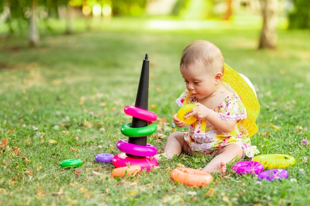 Een baby op het gazon of gras speelt met een piramide