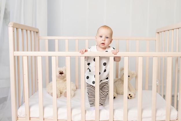 Een baby van 8 maanden staat in een wiegje met speelgoed in pyjama in een lichte kinderkamer en kijkt naar de camera