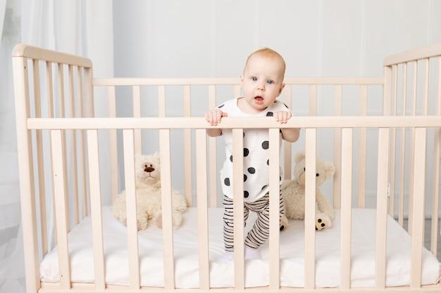 Een baby van 8 maanden staat na het slapen in een wieg met speelgoed in pyjama in een lichte kinderkamer en kijkt naar de camera, een plek voor tekst