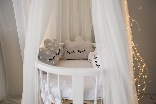Een babybedje met stoffen bovenkant en slinger