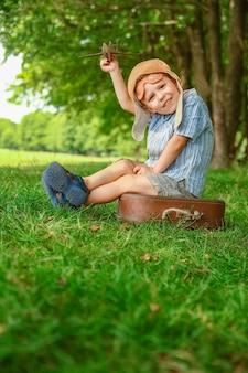 Een babyjongen bij het vliegtuig speelt op de natuur in het park. jongen op vakantiepiloot.