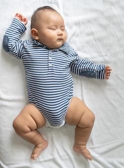 Een babyjongen in een gestreept overhemd slaapt in bed.