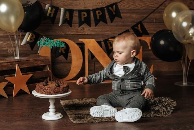 Een babyjongen in een grijs pak zit met een chocoladetaart op een feestelijke achtergrond