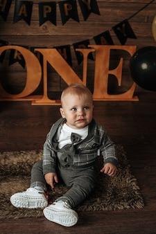 Een babyjongen in een grijs pak zit op een feestelijke achtergrond