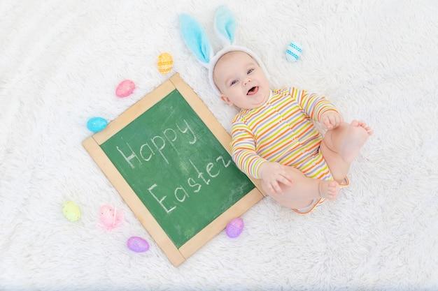 Een babyjongen in konijnenoren ligt op zijn hoofd met paaseieren en het opschrift happy easter, een schattige grappige lachende kleine baby. het concept van pasen.