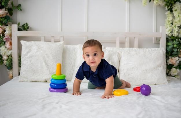 Een babyjongen ligt op handen en voeten op het bed en speelt met een piramidespeelgoed