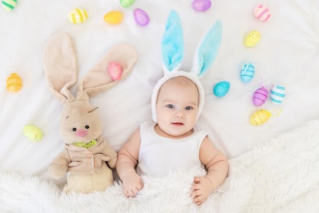 Een babyjongen met konijnenoren op zijn hoofd ligt in een wieg met een konijn speelgoed en paaseieren, een schattige grappige lachende kleine baby