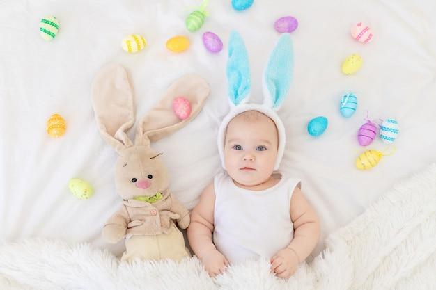 Een babyjongen met konijnenoren op zijn hoofd ligt in een wieg met een konijnenspeeltje
