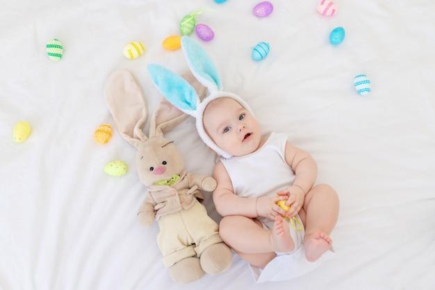 Een babyjongen met konijnenoren op zijn hoofd ligt in een wieg met een konijntje en paaseieren, een schattige grappige lachende kleine baby. pasen concept
