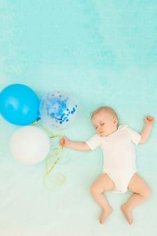 Een babyjongen slaapt en vliegt in een droom met ballonnen, ruimte voor tekst