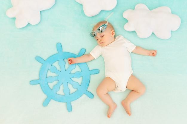 Een babyjongen slaapt met het stuur van een schip en een zwembril