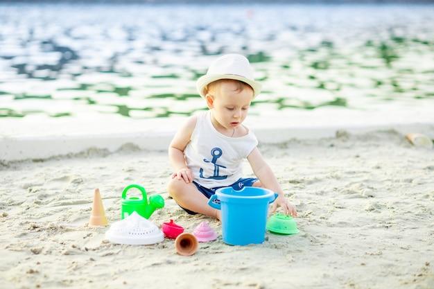 Een babyjongen van zes maanden speelt in het zand met speelgoed aan de kade door het water van de zee, het concept van recreatie en reizen