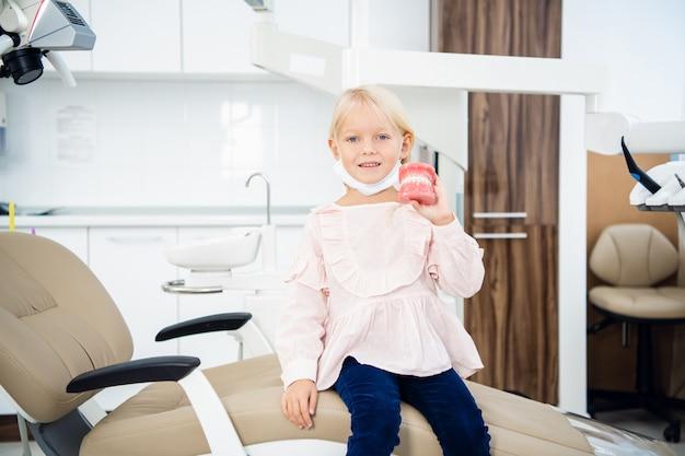 Een babymeisje glimlachend zitten in een tandheelkundige vergadering met een kunstmatige kaak in haar handen