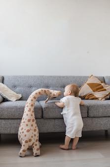 Een babymeisje in een jumpsuit van mousseline staat met een knuffelgiraf bij een grijze bank in de woonkamer