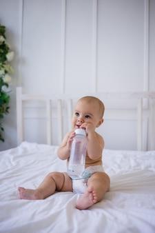 Een babymeisje in een luier houdt een fles water vast en zit op een wit bed