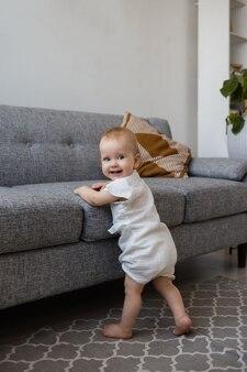 Een babymeisje in een mousseline jumpsuit staat naast een grijze bank in de kamer en lacht