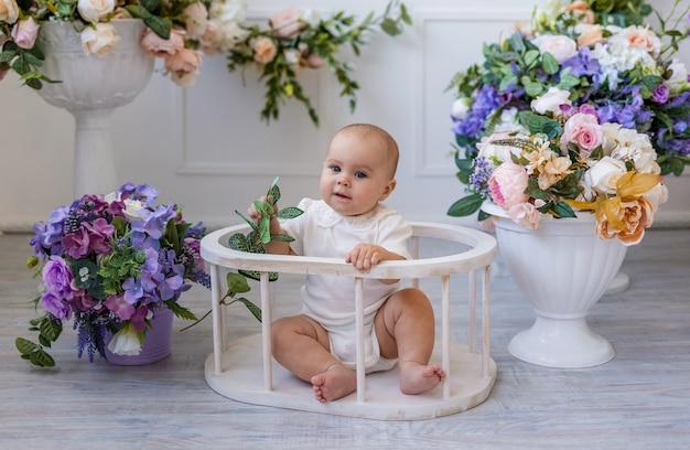 Een babymeisje in een wit rompertje met kant zit in een stoel op een achtergrond met bloemen