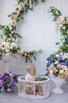 Een babymeisje in een witte bodysuit zit op een achtergrond met bloemen