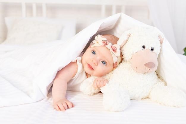 Een babymeisje ligt onder een deken met speelgoed van een teddybeer en lacht thuis op een wit katoenen bed