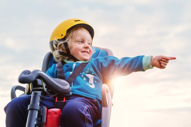Een babymeisje met een helm die een helm draagt, zit in een kinderfietsstoel en maakt een wijsgebaar