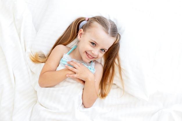 Een babymeisje slaapt of is 's ochtends wakker geworden op een bed thuis op een wit katoenen bed en lacht zoet