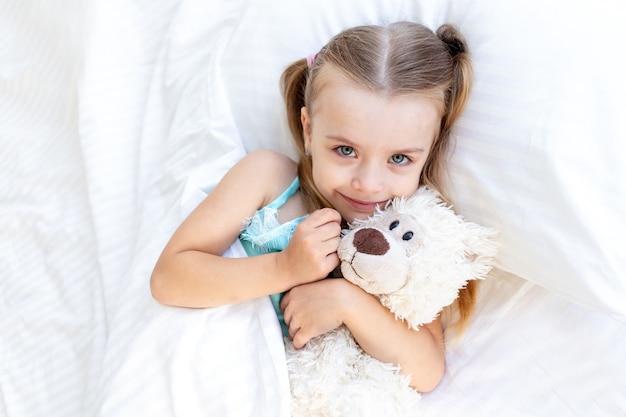 Een babymeisje slaapt of werd 's ochtends wakker op het bed thuis op een wit katoenen bed, knuffelde een teddybeer in haar handen en glimlachte liefjes
