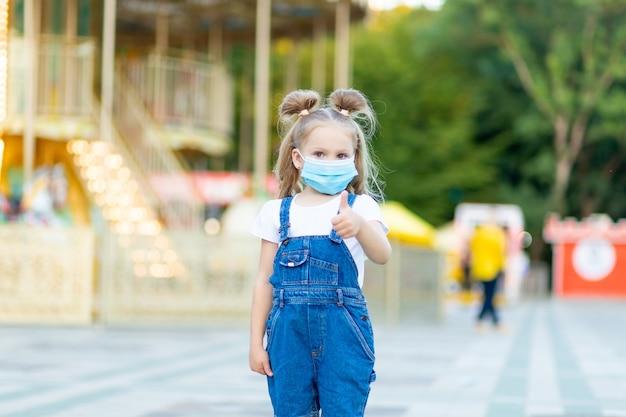 Een babymeisje staat in een pretpark met een beschermend medisch masker