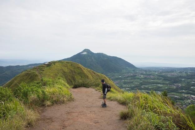 Een backpacker man reist alleen, met rugzak in de bergen