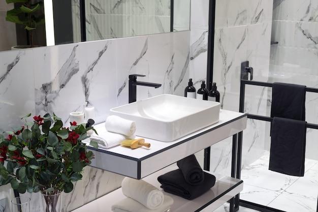 Een badkamer in moderne stijl met wastafel in de kleuren zwart en wit gekleurd.