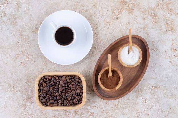 Een bakje met kommetjes suiker en gemalen koffiepoeder naast een kopje koffie en een bakje koffiebonen