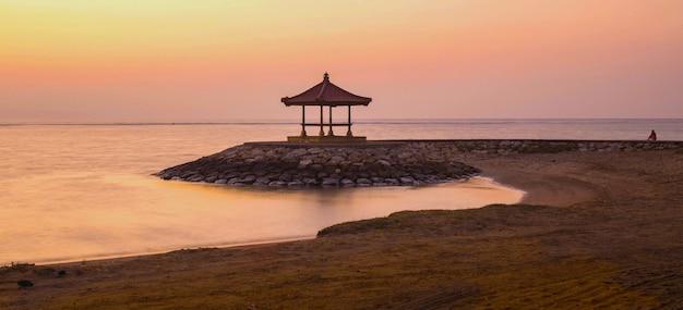 Een balinese pagode op het strand van sanur.