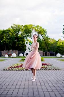 Een ballerina in een lange roze zijden jurk draait in een dans in het park in zomerballet in het stadsland...