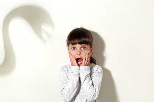 Een bang klein kind kleedt zich in witte vrijetijdskleding en schreeuwt luid, bedekt de wangen met handpalmen, wordt bang door de schaduw van een enorme slang, geïsoleerd over een grijze muur.