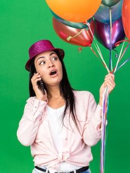 Een bang uitziende jonge, mooie vrouw met een feesthoed die ballonnen vasthoudt, spreekt op de telefoon geïsoleerd op een groene muur