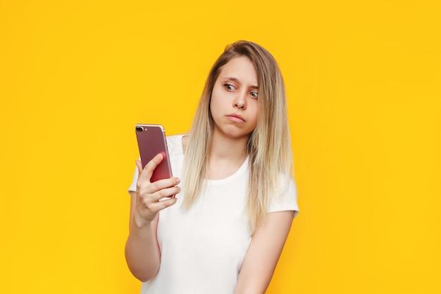 Een bange jonge blanke blonde vrouw in een wit t-shirt met een mobiele telefoon in haar hand kijkt verdacht naar de inkomende oproep van een onbekend nummer op een felle gele muur