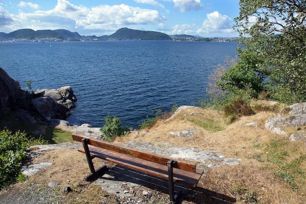 Een bank staat op de top van een berg en kijkt uit over de fjord