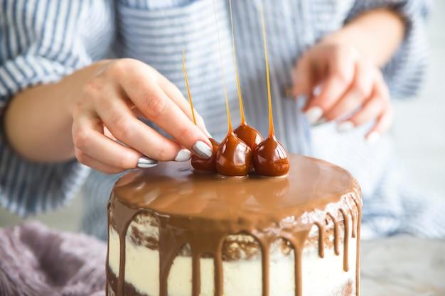 Een banketbakker decoreert een kant-en-klare cake