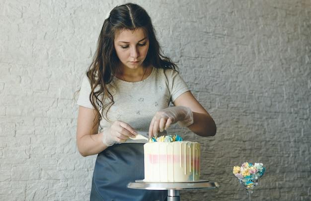 Een banketbakker maakt met haar eigen handen een bruidstaart en legt met slagroom kleurige versieringen op de taarten. voorbereiding op de viering.