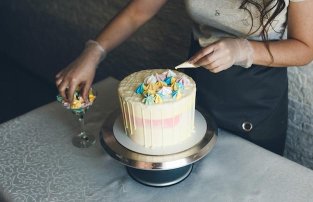 Een banketbakker maakt met haar eigen handen een bruidstaart en zet kleurrijke versieringen op de taarten met room