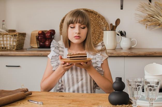 Een banketbakkersmeisje houdt een bord dessert in haar handen en sloot haar ogen met plezier