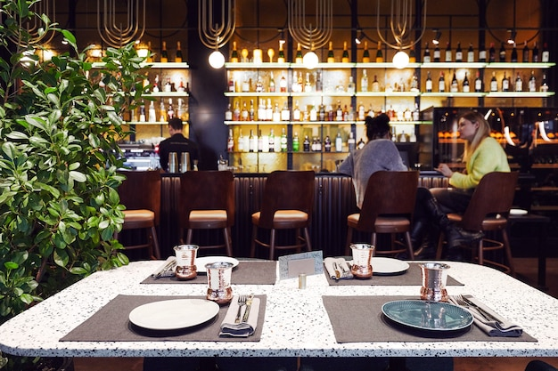 Een bar met mensen en obers met een toog en veel alcohol het interieur is in een moderne stijl