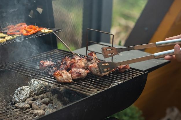 Een barbecuegrill met lekkere sappige steaks wordt gegrild boven een open vuur.
