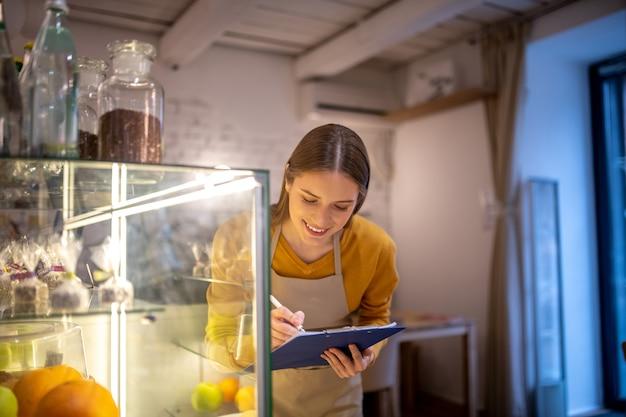 Een barista die desserts controleert in de vitrine