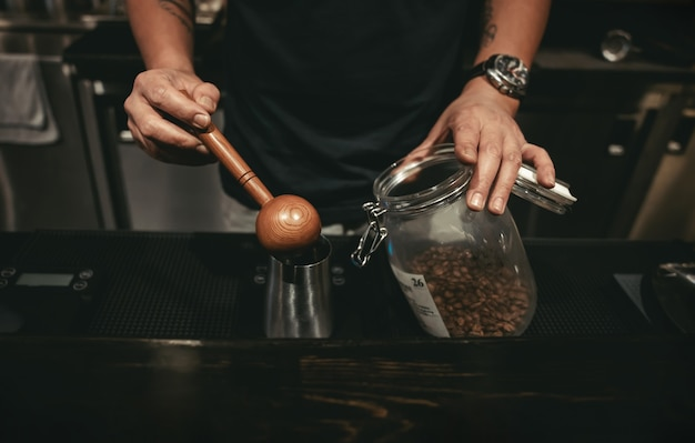 Een barista die koffie maakt in het café. met behulp van houten lepel om koffiebonen te meten