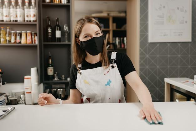 Een barista in een medisch zwart gezichtsmasker glimlacht en maakt de bar in een koffiewinkel schoon