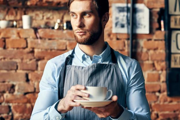 Een barista poseert met een koffiekopje