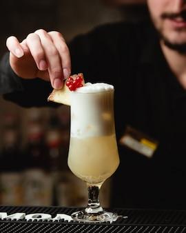 Een barman die ananassap met bessen en ananasplak verfraait.